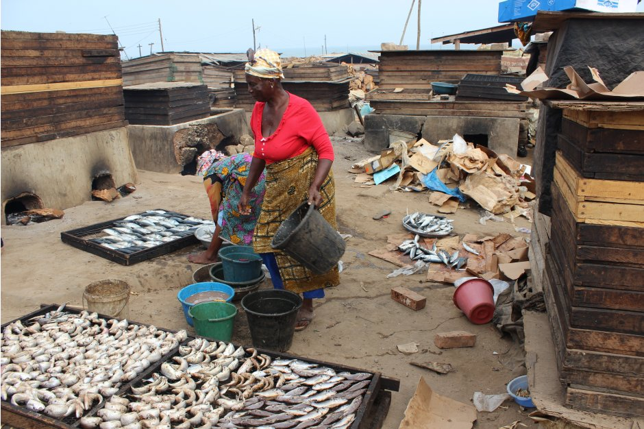 A local woman smokes fish using traditional methods